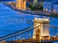 stock-photo-river-view-of-budapest-at-evening-illuminated-chain-bridge-and-parliament-building-119747956