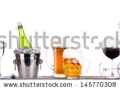 stock-photo-grapes-ice-bucket-with-bottle-of-champagne-and-glass-on-a-table-isolated-on-a-white-baclground-145770308