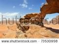 stock-photo-natural-rock-bridge-and-panoramic-view-of-wadi-rum-desert-jordan-73530958