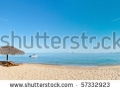 stock-photo-tropical-beach-panorama-with-deckchairs-umbrellas-boats-and-palm-tree-57332923