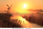 stock-photo-dutch-sunrise-with-traditional-windmill-and-a-canal-in-the-spring-fog-74120035