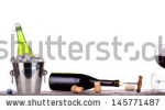 stock-photo-grapes-ice-bucket-with-bottle-of-champagne-and-glass-on-a-table-isolated-on-a-white-baclground-145771487